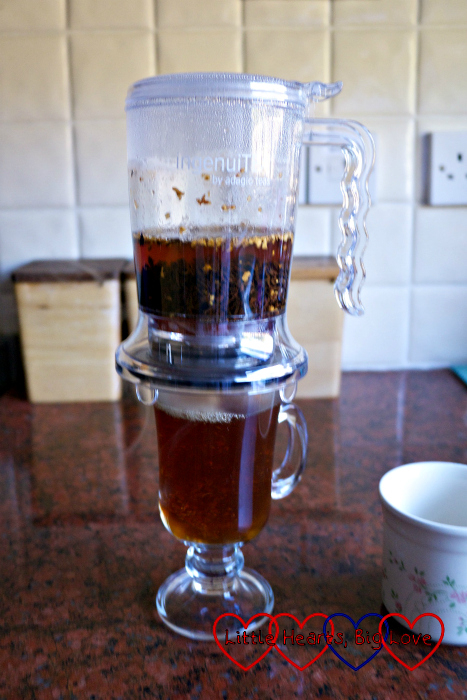 Tea emptying from the IngenuiTEA teapot into a glass mug