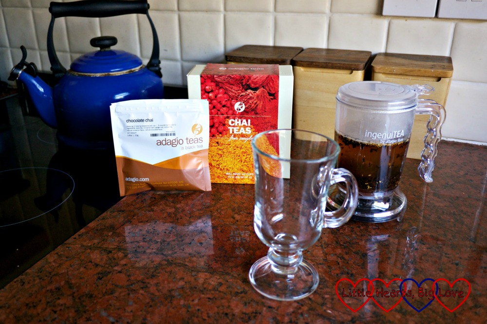 Chocolate chai tea brewing in the IngenuiTEA teapot next to the sample box and packet and a glass mug