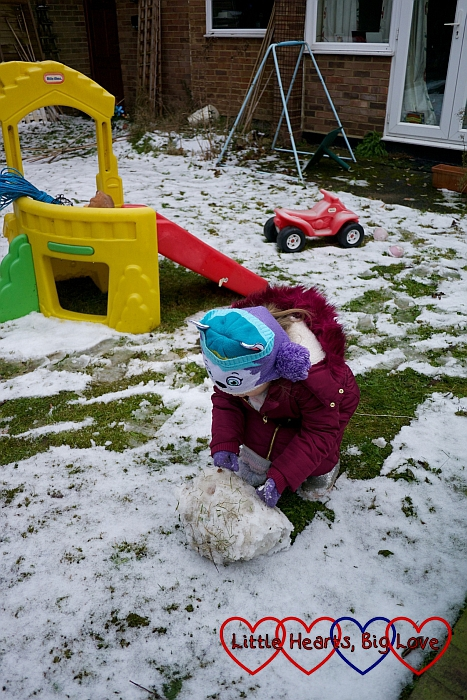 Sophie rolling up the snow in the garden to make the snowman