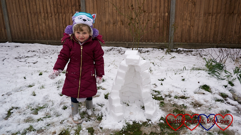 Sophie standing next to the finished igloo