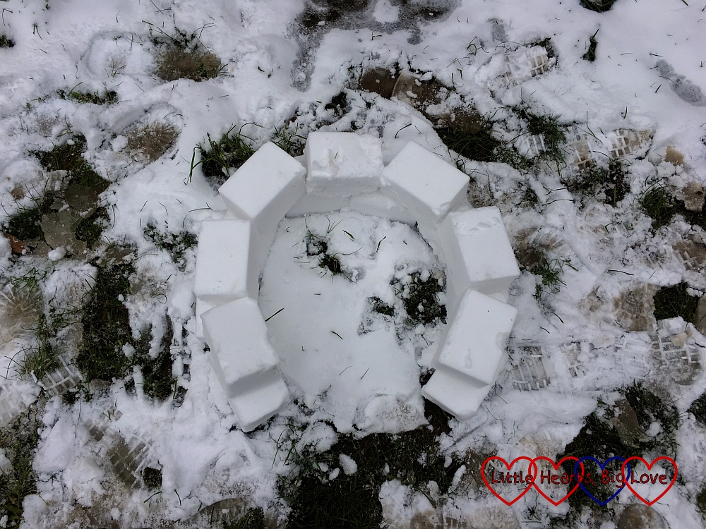Lining up the snow bricks on the second layer of the igloo