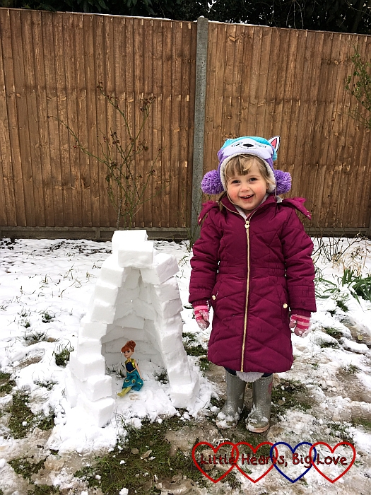 Sophie standing next to her finished igloo with her Anna doll inside