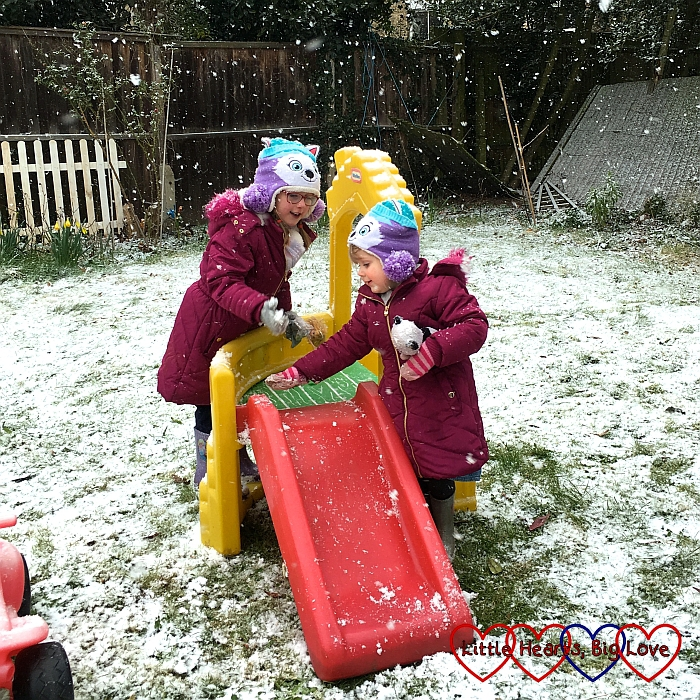 Jessica and Sophie clearing the snow from their slide in the garden