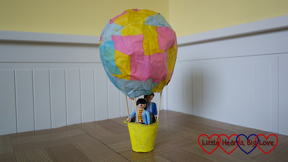 papier-mâché hot air balloon with Playmobil figures inside the cardboard basket