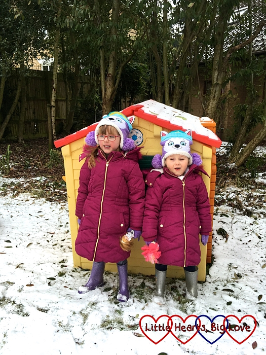 Jessica and Sophie standing in front of their playhouse in the snow