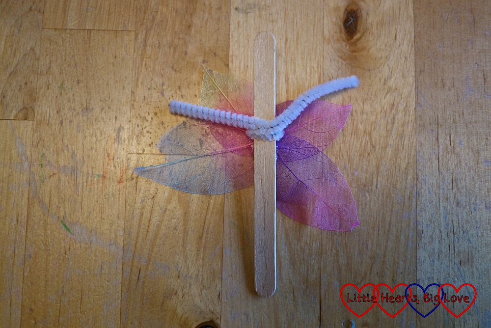 A craft stick with a pipe cleaner wrapped around it and leaf shapes stuck to the back