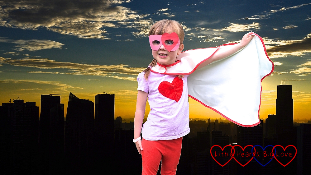 Jessica wearing a superhero mask with a superhero cape against a backdrop of buildings