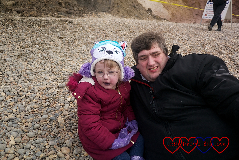 Jessica and Daddy having a snuggle on the beach at Alum Bay