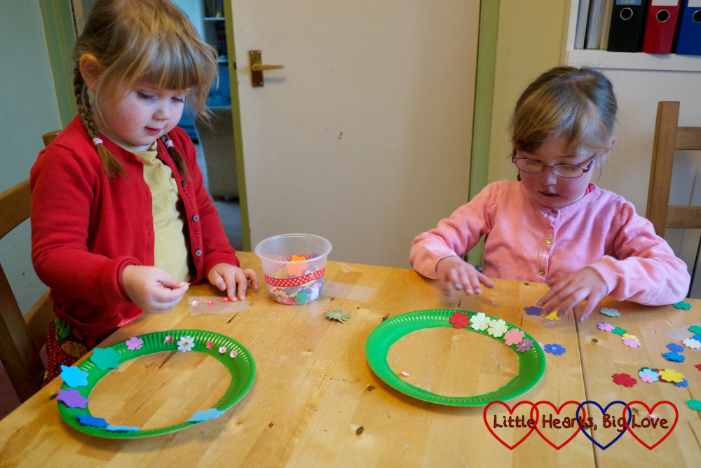 Jessica and Sophie sticking flower shapes on their paper plates