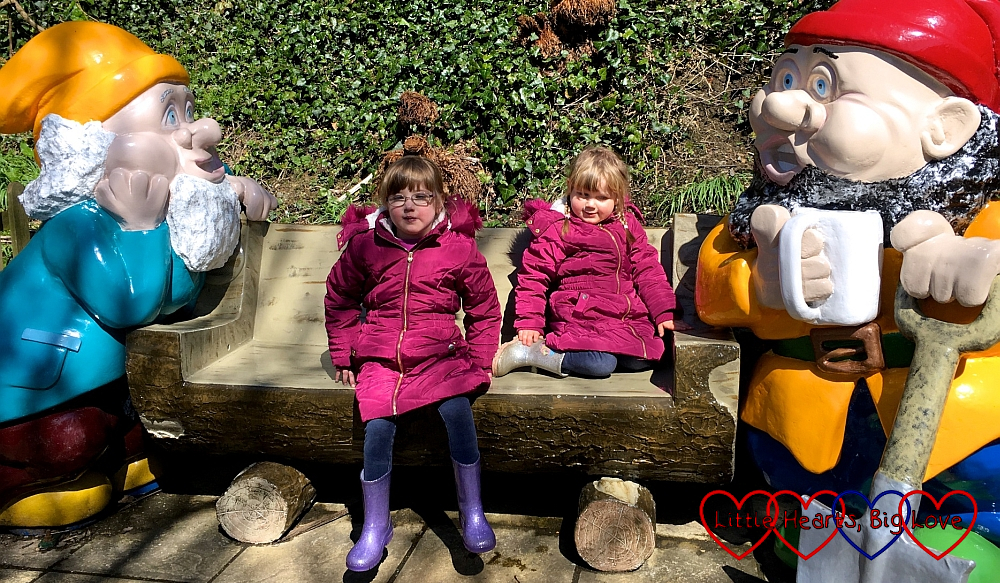 Jessica and Sophie sitting on a bench with two giant gnomes at Blackgang Chine
