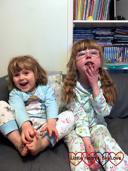 Jessica and Sophie sitting together on the sofa in their pyjamas