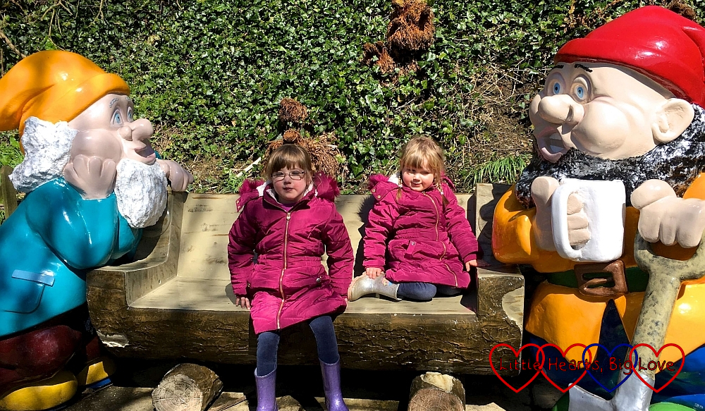 Jessica and Sophie sitting with the giant gnomes at Blackgang Chine
