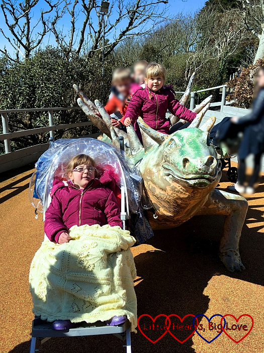 Sophie sitting on one of the dinosaurs in Restricted Area 5 with Jessica next to her in the buggy