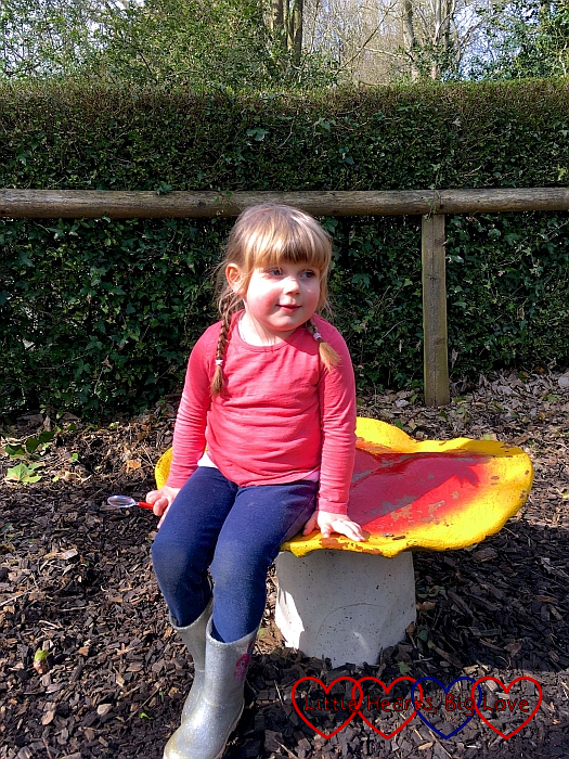 Sophie sitting on a toadstool at Fairyland