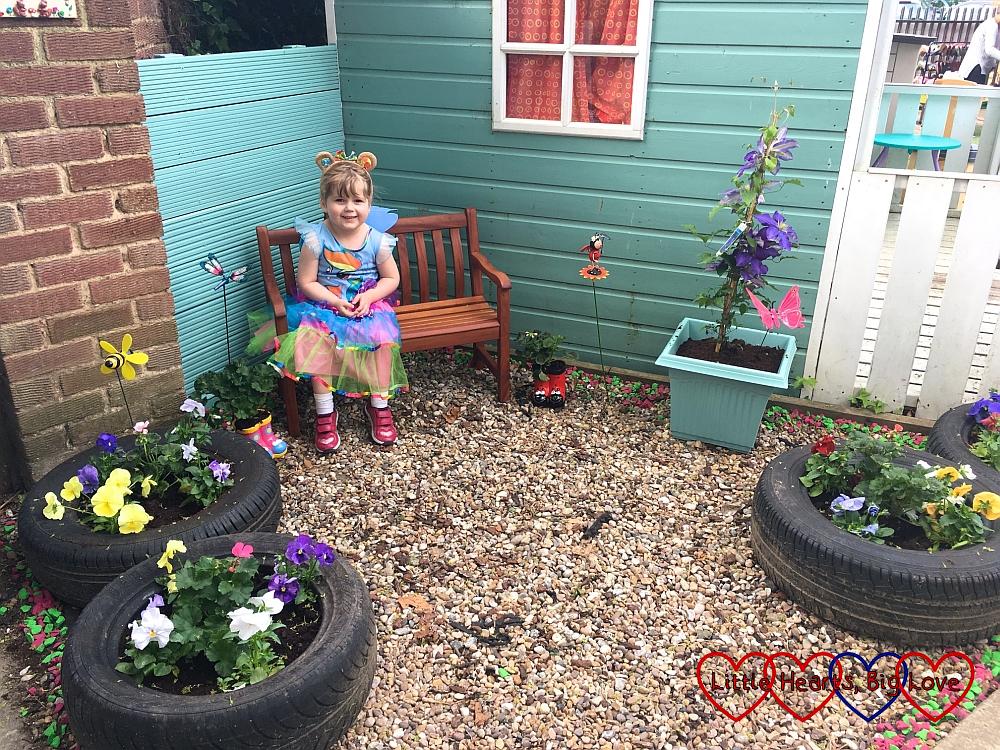 "Sophie sitting on a bench in ""Jessica's garden"""