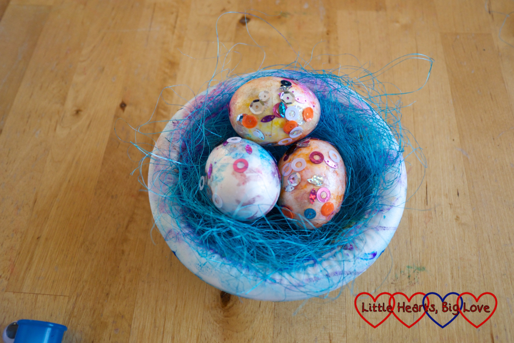 The paper bowl filled with shredded blue paper and sparkly polystyrene eggs