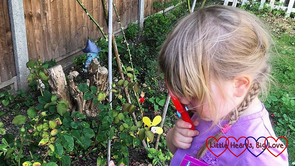 Sophie taking a closer look in the garden with her magnifying glass
