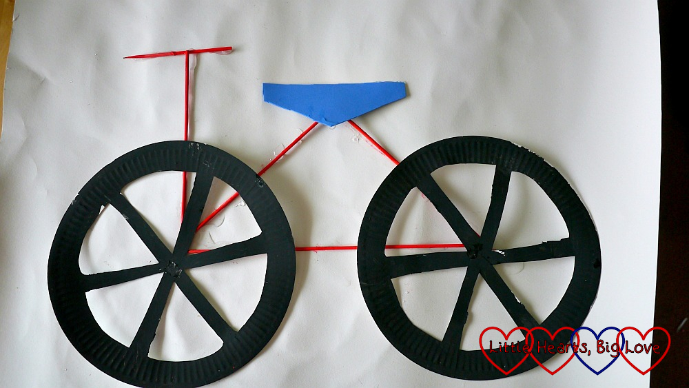 The finished bicycle picture with the paper plate wheels, wooden skewer frame and craft foam saddle