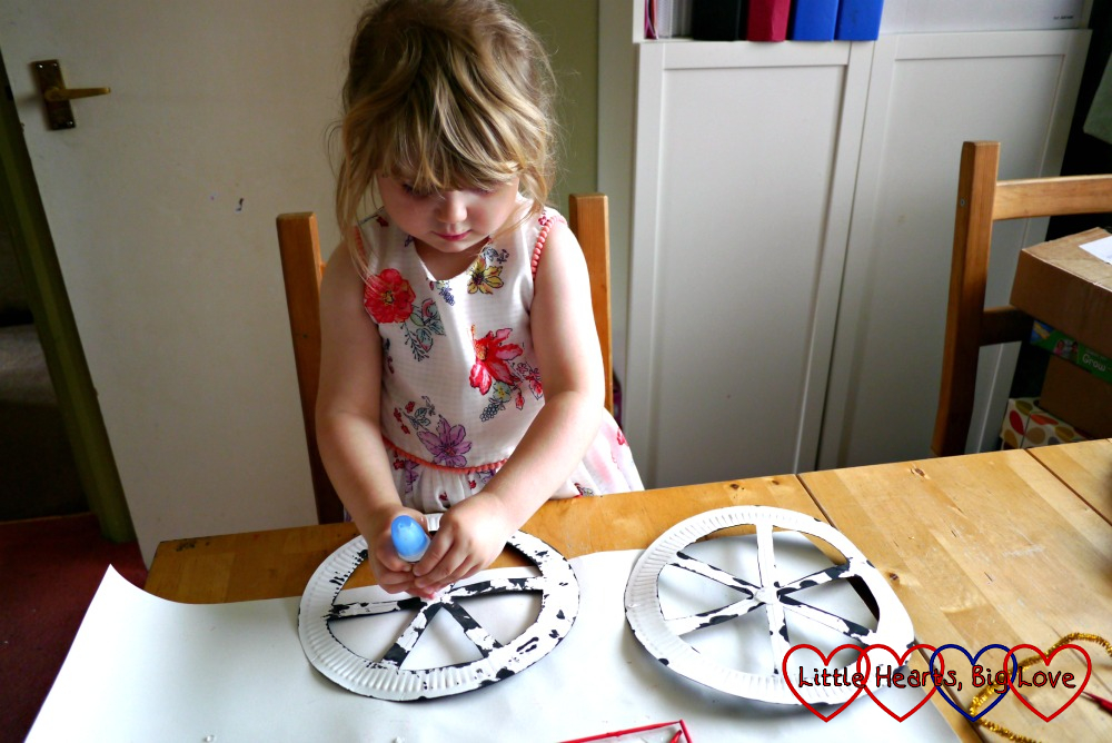 Sophie glueing the paper plate bicycle wheels