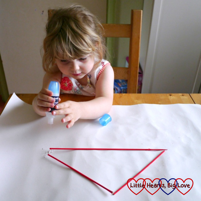 Sophie glueing the wooden skewers into a triangle shape