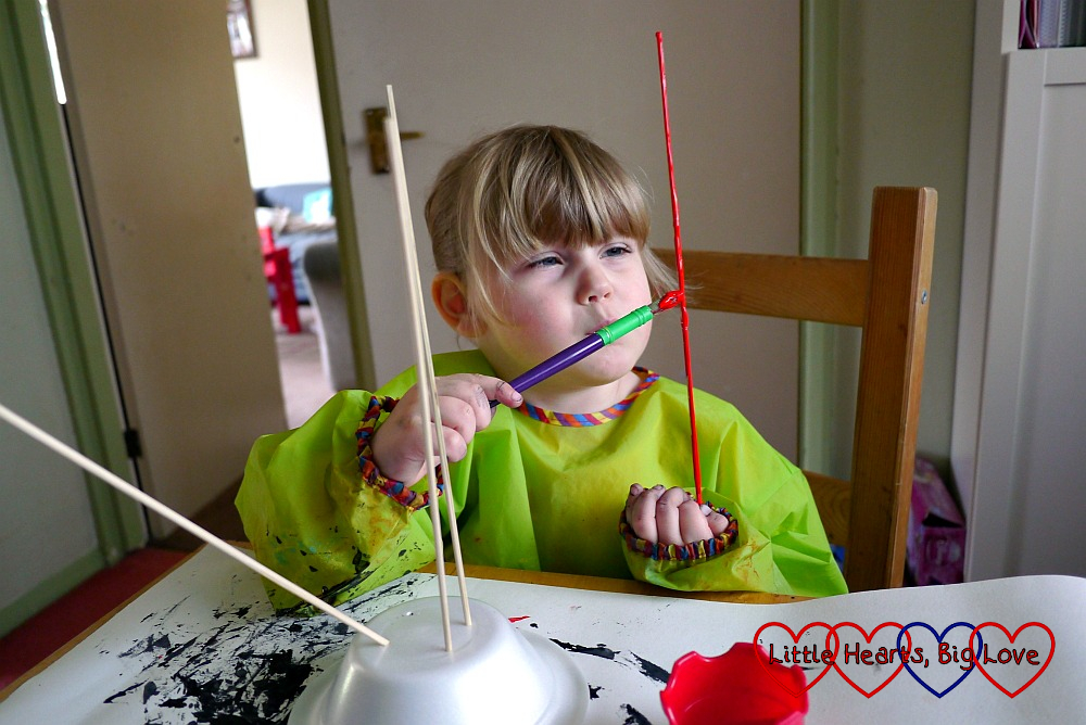 Sophie painting the wooden skewers with red paint