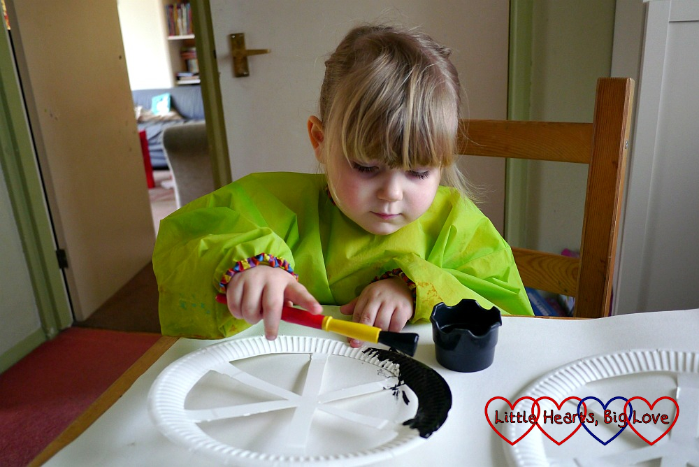 Sophie painting the paper plates with black paint