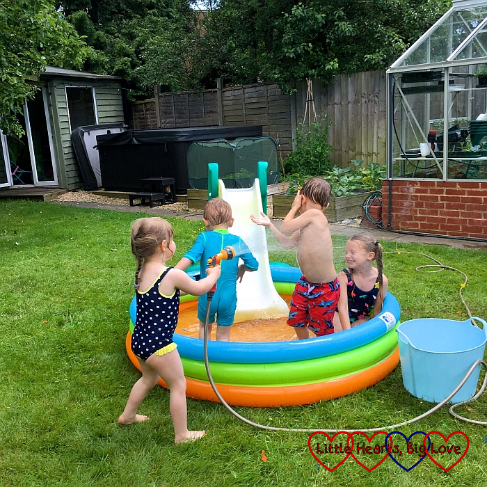 Sophie playing with friends in a paddling pool