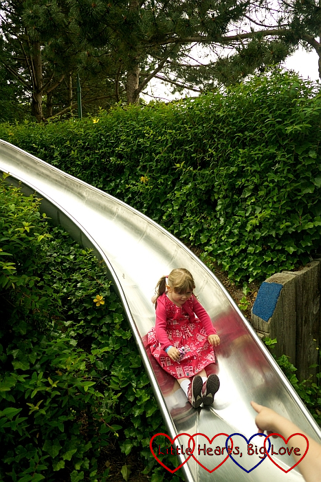 Sophie going down the slide on the walk down the hill into Legoland