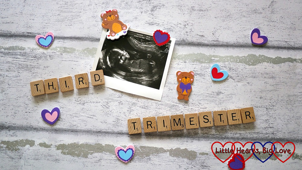 "A scan photo surrounded by hearts, teddy bears and Scrabble letters spelling out ""third trimester"""