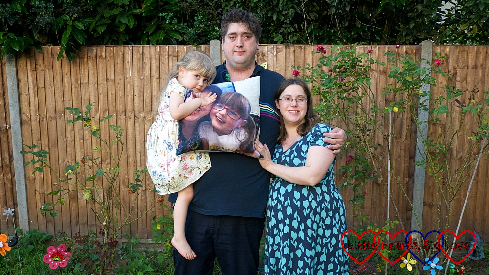 Me, hubby and Sophie in the garden holding the cushion with Jessica's picture on