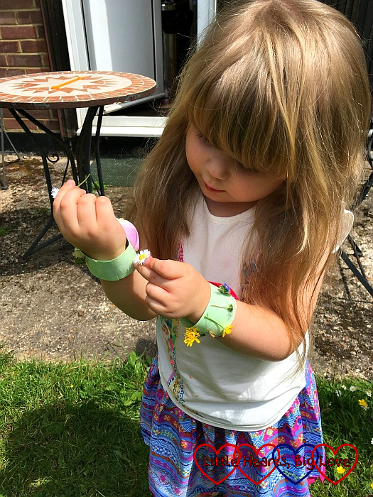 Sophie sticking daisies to her nature bracelet