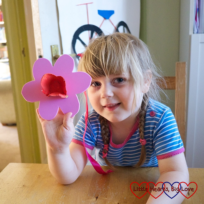 Sophie holding up a flower shape with a painted egg cup stuck to the middle
