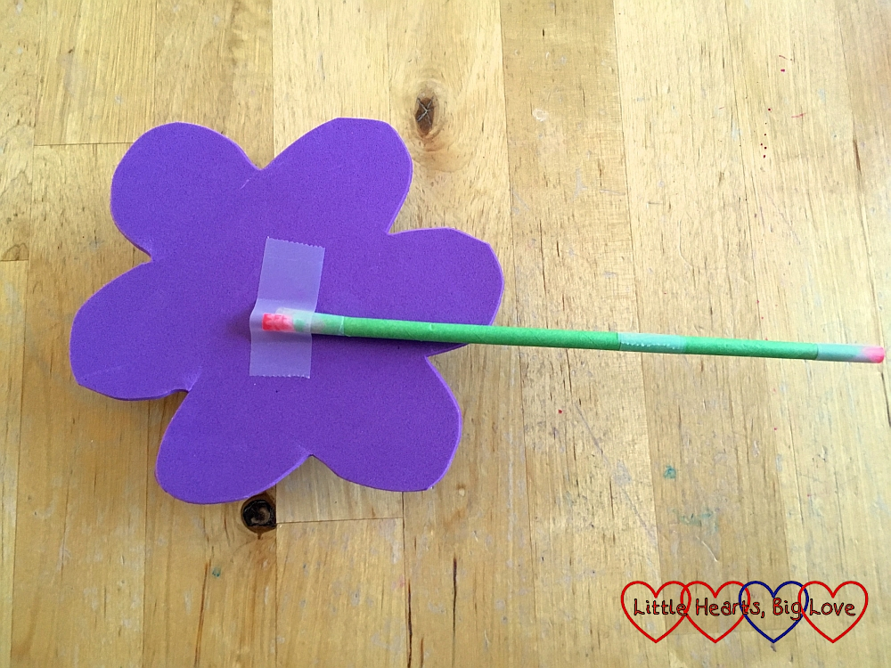 A straw stuck to the back of a craft foam flower