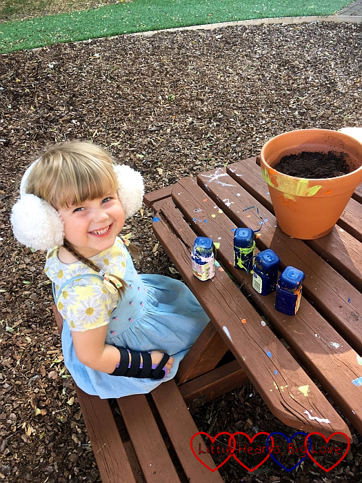 Sophie wearing a pair of white ear muffs while painting a plant pot