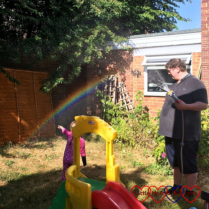 Hubby and Sophie in the garden looking at the rainbow formed by the spray from the hose