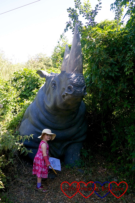 Sophie standing next to a big model of a rhino