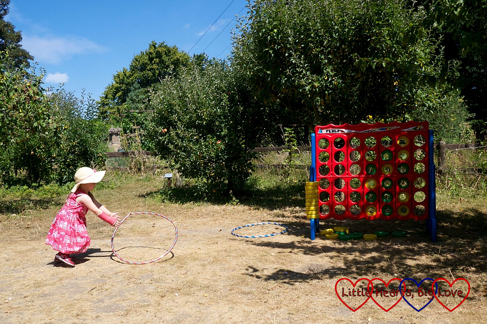 Sophie spinning a hula hoop next to a giant connect-4 in the orchard