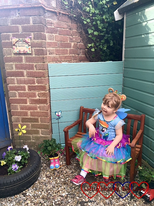 Sophie sitting on the bench in Jessica's garden