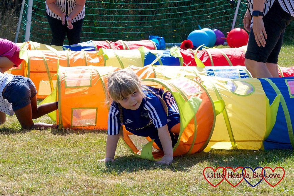 Sophie crawling through the tunnel on the obstacle race