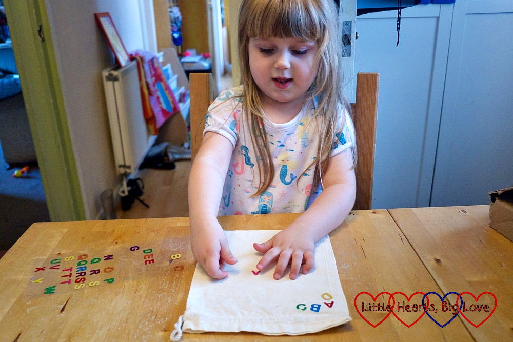 Sophie putting letter stickers on the fabric bag