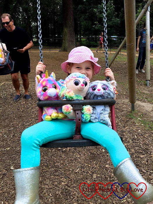 Sophie with three of her soft toys on the swing at the park