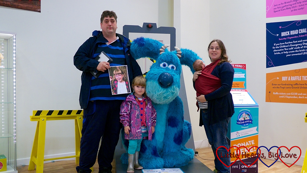 "Me, hubby, Sophie and Thomas with a picture of Jessica at ""Gromit P. Sullivan (Sulley)"""