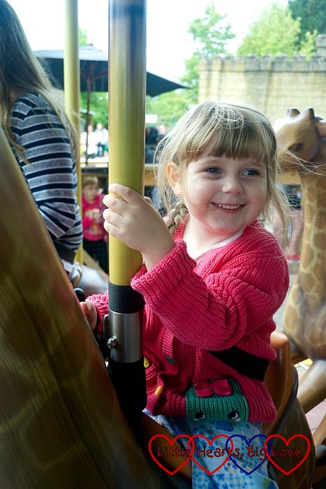 Sophie riding a giraffe on the Adventure Tree carousel