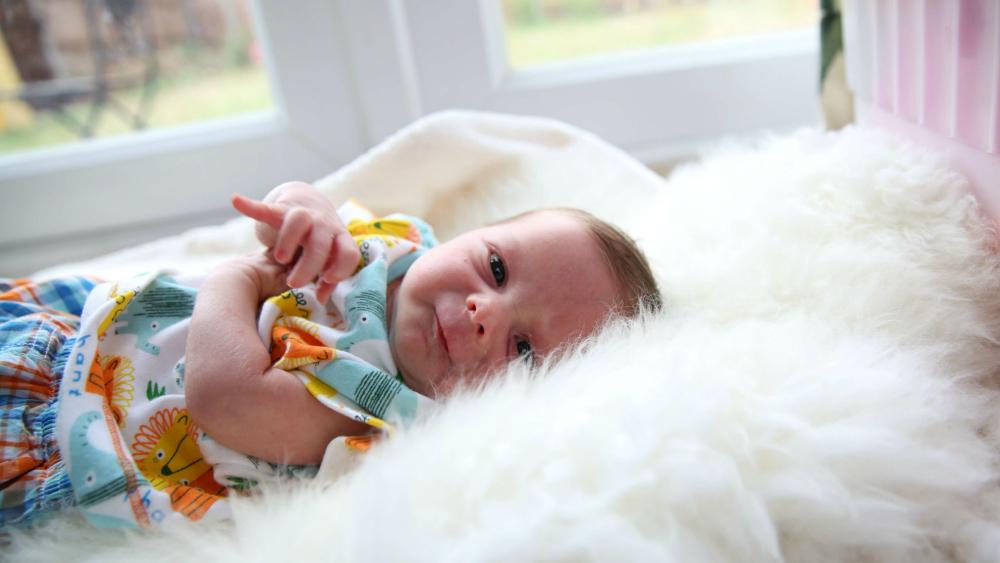 Baby Thomas lying on a sheepskin rug