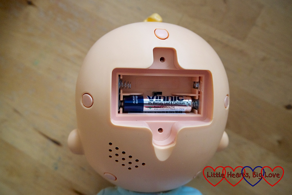 The battery compartment with the on/off switch inside the doll's head
