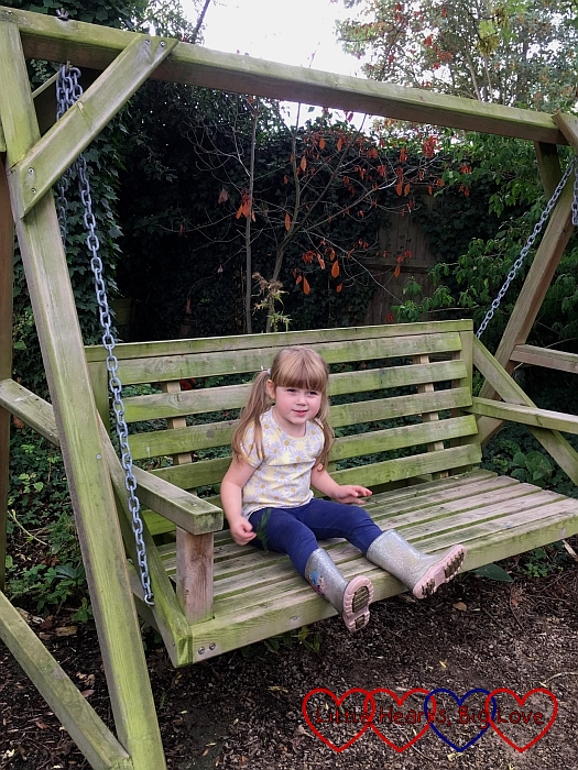 Sophie sitting on a wooden swing seat