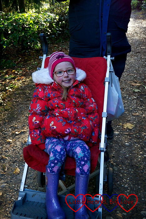 Jessica in her red winter coat and wooly hat, sitting in her buggy