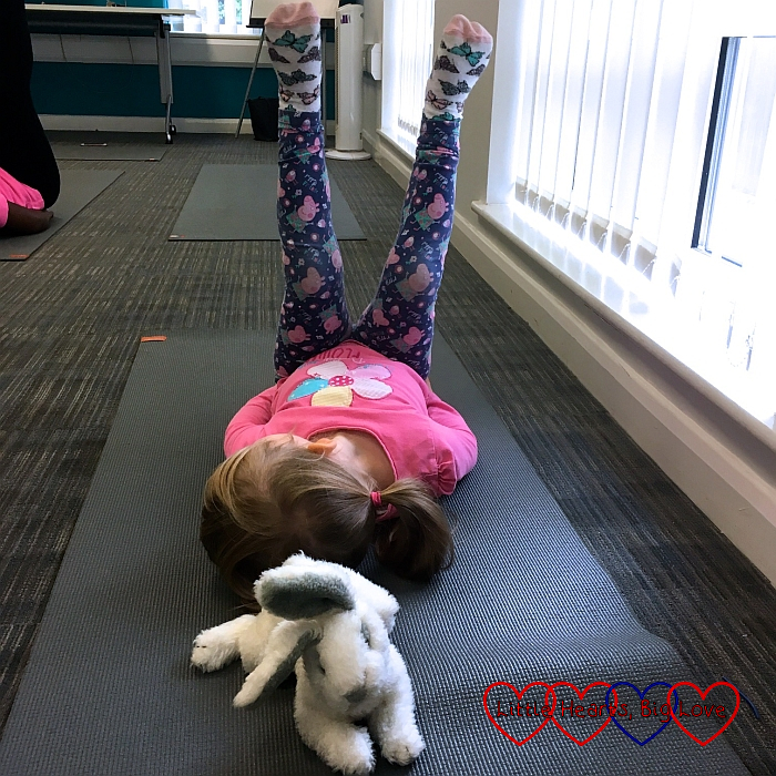 Sophie lying on her back with her legs in the air with the class bunny in the foreground