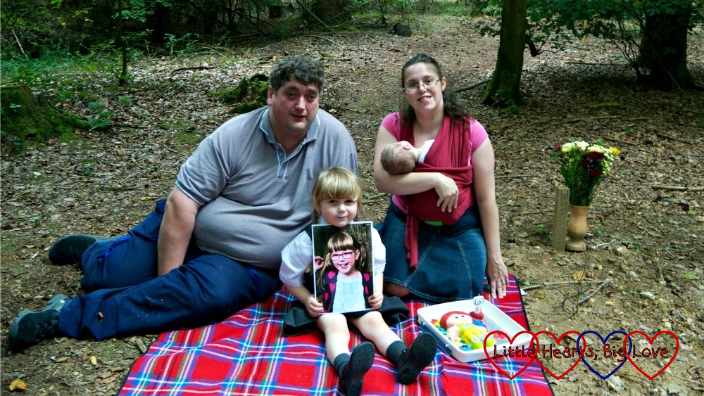 "Hubby, Sophie, me and Thomas sitting on a picnic blanket at Jessica's forever bed with a photo of Jessica and her ""Kerry"" birthday cake"