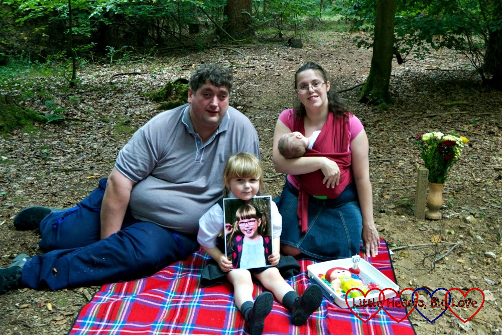 """Hubby, Sophie, me and Thomas sitting on a picnic blanket at Jessica's forever bed with a photo of Jessica and her """"Kerry"""" birthday cake"""